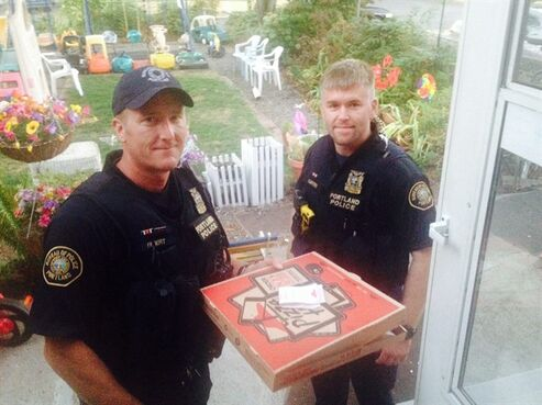 In this photo taken Sept. 1, 2014, and provided by Steve Huckins, Portland police officers Michael Filbert, left, and Royce Curtiss, right, pose after completing a pizza delivery to the Huckins home after a Pizza Hut delivery driver was hurt in a crash in Portland, Ore. Huckins and his wife were concerned when the officers showed up at their home, but they started laughing when they received the pizza. They're thanking the officers for going out of their way. The driver hurt his neck and back in the collision at an intersection, but is now okay. (AP Photo/Steve Huckins)
