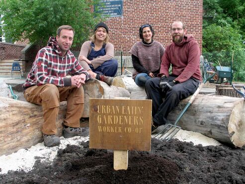 (Left to right) Urban Eatin' Gardeners Worker Co-op members Tommy Allen, Natalie Dyck, Naomi Audia and Mark Klassen sit on reclaimed and debarked elm wood from Wood Anchor, installed as part of the in progress outdoor classroom at Grosvenor School. Not pictured: Urban Eatin' worker Paolo Riva.