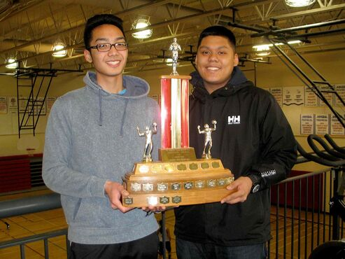 Sisler High School varsity volleyball players Jan Salceda (left) and Kyle Ordonez show off the team's Zone 1 championship trophy.