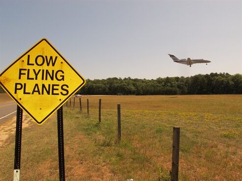 In this Wednesday, Aug. 20, 2014 photo, a small jet approaches the runway at East Hampton Town Airport. Residents across eastern Long Island are complaining about the noise generated from jets, helicopters and other aircraft that land at the small municipal airport, which is situated in the heart of the summer playground for the rich and famous. (AP Photo/Frank Eltman)