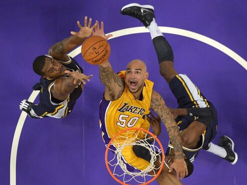 Utah Jazz center Derrick Favors, left, and forward Jeremy Evans, right, battle for a rebound with Los Angeles Lakers center Robert Sacre during the first half of a preseason NBA basketball game, Sunday, Oct. 19, 2014, in Los Angeles. (AP Photo/Mark J. Terrill)
