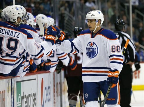 Edmonton Oilers defenseman Brandon Davidson, right, is congratulated by teammates after scoring a goal against the Colorado Avalanche in the first period of an NHL hockey game Monday, March 30, 2015, in Denver. (AP Photo/David Zalubowski)