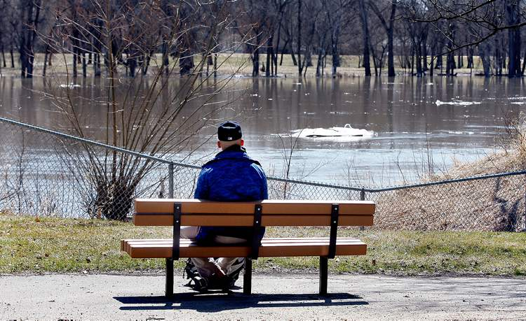 Jeremy Botelho relaxes in the sun, watching ice float by on the swollen Red River at Kildonan Park last Friday.