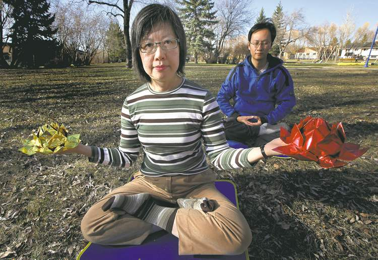 Maria Cheung meditates while holding lotus flowers as HuaiDong Wang meditates behind her. The pair are practitioners of Falun Gong.