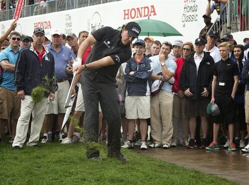 Phil Mickelson hits out of the rough and onto the 18th green during the rain delayed second round of the Honda Classic golf tournament, Saturday, Feb. 28, 2015 in Palm Beach Gardens, Fla. (AP Photo/J Pat Carter)