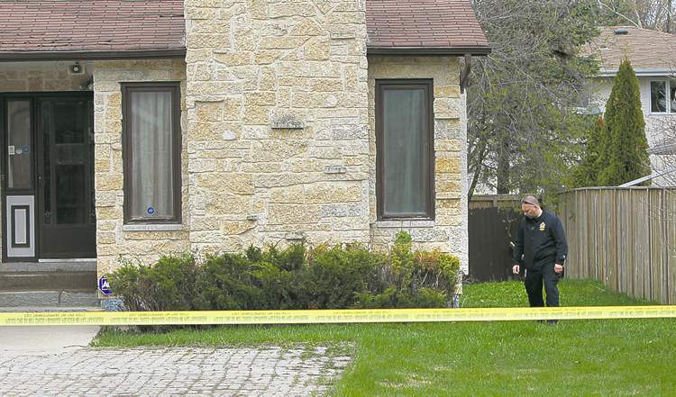 A police officer at the secured scene in the 4300 block of Roblin Boulevard Friday.