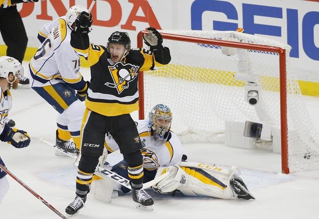 Pittsburgh Penguins' Jake Guentzel front celebrates a goal by teammate Evgeni Malkin in front of Nashville Predators goalie Pekka Rinne during the first period in Game 1 of the NHL hockey Stanley Cup Final Monday