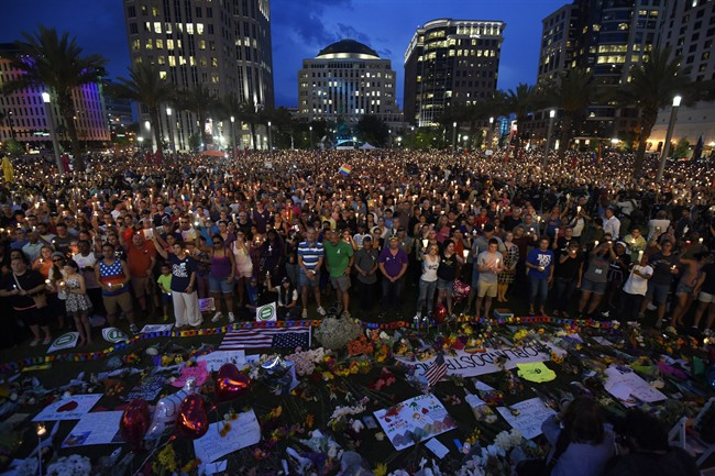 Thousands gather outside the Dr. Phillips Performing Arts Center for a vigil Monday, June 13, 2016 in Orlando, Fa. A large crowd gathered to remember the Pulse nightclub shooting victims early Sunday. (Chris Urso/Tampa Bay Times via AP) MANDATORY CREDIT