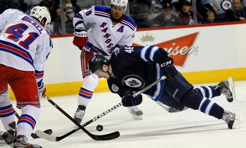 Winnipeg Jets' Spencer Machachek goes in for a close look at the puck in second-period action Wednesday at Winnipeg's MTS Centre. March 28, 2012 - (Phil Hossack / Winnipeg Free Press)