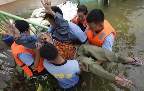 Silvestra Baguio, 83, reacts as she is carried along a flooded area by police while they transfer her to a temporary evacuation center at Malabon city, north of Manila, Philippines, Wednesday Aug. 1, 2012. The slow-moving Typhoon Saola displaced 154,000 people in the country.  AP Photo / Aaron Favila