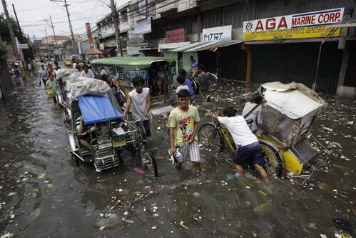 Filipinos wade along garbage-laden floodwaters at Navotas city, north of Manila, Philippines, Wednesday, Aug. 1, 2012. Fierce winds and heavy rains from the slow-moving Typhoon Saola battered the country, displacing 154,000 people.  AP Photo / Aaron Favila