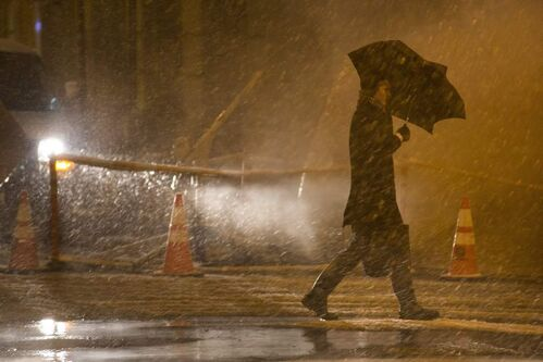 A pedestrian walks into the wind and snow in the financial district, Wednesday, Nov. 7, 2012, in New York. Residents of New York and New Jersey who were flooded out by Superstorm Sandy are waiting with dread Wednesday for the second time in two weeks as another, weaker storm heads toward them and threatens to inundate their homes again or simply leave them shivering in the dark for even longer. (AP Photo/John Minchillo)