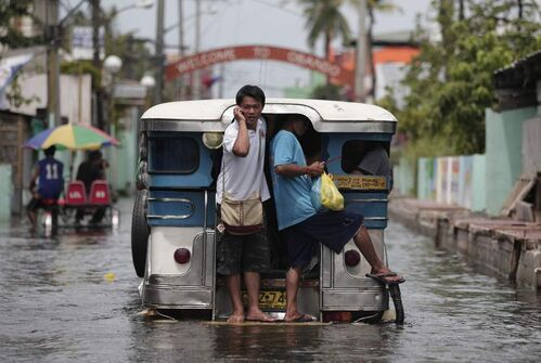 A Filipino man answers a call on his mobile phone as he rides a partly submerged passenger jeep in Valenzuela city, north of Manila, Philippines Tuesday July 31, 2012. Typhoon Saola dumped torrents of rain as it swept past the Philippines, killing at least seven people and displacing more than 20,000 others by Tuesday.  AP Photo / Aaron Favila