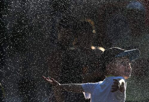 Kaleb Sarrasin , 3, cools off in a mist fountain at the Fringe Festival MTS Outdoor Stage in Old Market Square. 