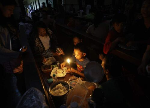 An evacuee takes his dinner under candelight as electricity was cut due to flooding at a church that is converted into a temporary evacuation center in Quezon City, north of Manila, Philippines, on Tuesday Aug. 7, 2012. Relentless rains submerged half of the sprawling Philippine capital, triggered a landslide that killed several people and sent emergency crews scrambling Tuesday to rescue tens of thousands of residents who called media outlets pleading for help. AP Photo / Aaron Favila