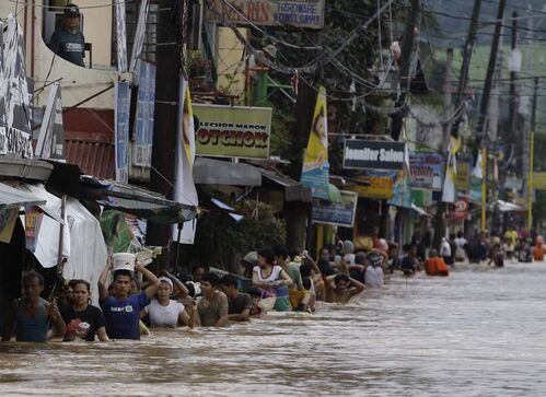Residents cross a flooded road in Marikina City, east of Manila, Philippines, on Wednesday Aug. 8, 2012. Widespread flooding that killed at least 23 people, battered a million others and paralyzed the Philippine capital briefly eased Wednesday, allowing rescuers on rubber boats to reach a large number of distressed residents still marooned in submerged villages. AP Photo / Aaron Favila