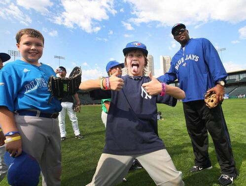 Luc Laurin (centre), 10, from the Charleswood Twins shows his excitement being next to Former Toronto Blue Jays and World Series winning outfielder Jesse Barfield at Shaw park during the Blue Jays Honda Super Camp.
