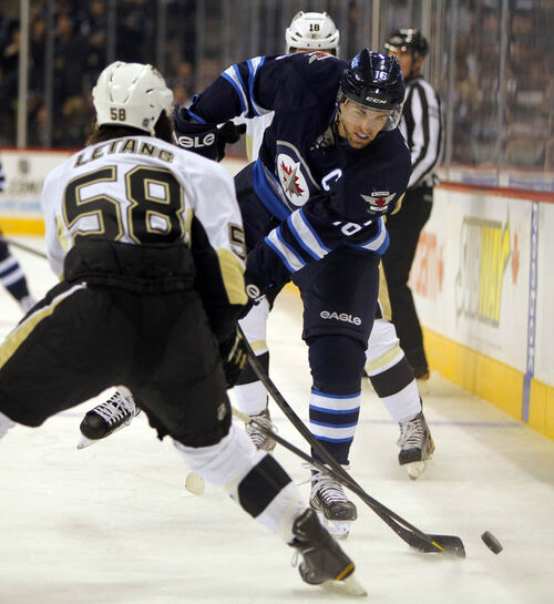 Jets captain Andrew Ladd tries to get past Penguins' Kris Letang.