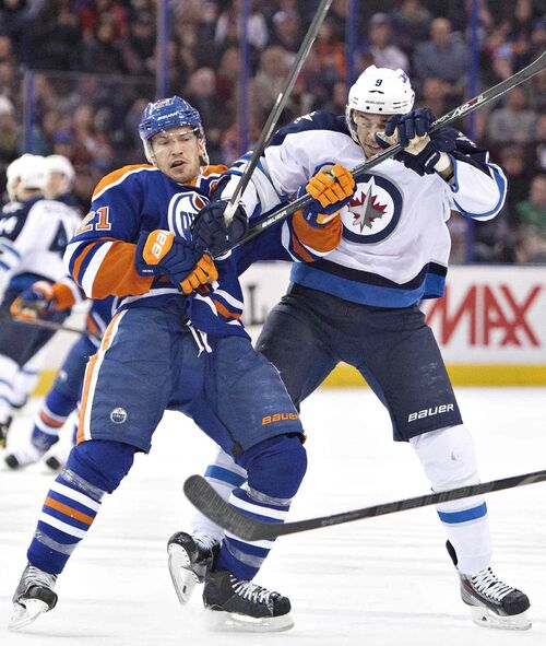 Winnipeg Jets' Evander Kane (9) and Edmonton Oilers' Andrew Ference (21) battle during first period NHL hockey action in Edmonton, Alta., on Monday.