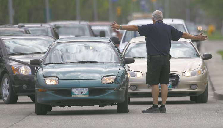 A Blue Bofmbers staffer directs traffic as rows of cars back up on the University of Manitoba campus prior to the team's first pre-season game Wednesday.