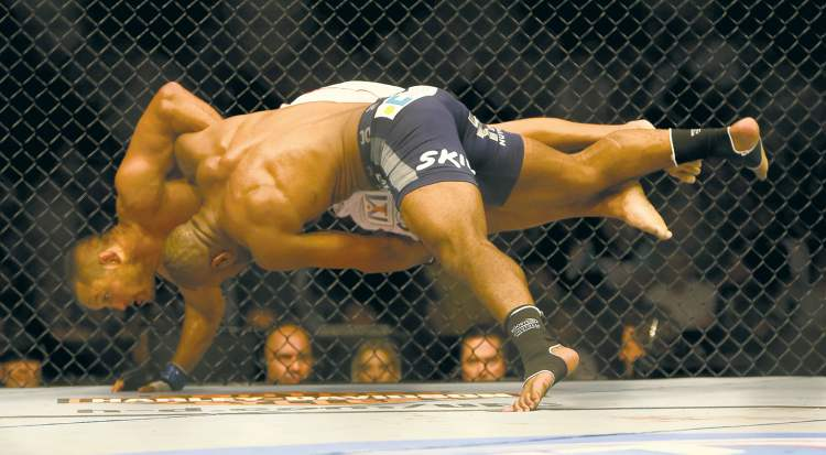 Rashad Evans drives Dan Henderson to the floor on the way to a judges decision during their bout at UFC 161 in Winnipeg Saturday.