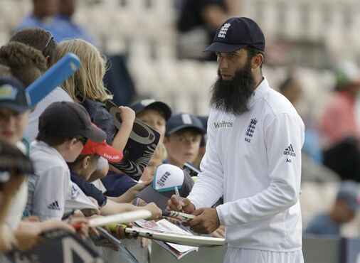 "England's Moeen Ali signs autographs on the edge of the boundary as his side field during the second day of the third cricket test match of the series between England and India at The Ageas Bowl in Southampton, England, Monday, July 28, 2014. England cricketer Moeen Ali is unlikely to face punishment after being photographed wearing wristbands saying ""Save Gaza"" and ""Free Palestine"" while batting in the third test against India. The England and Wales Cricket Board says ""we don't believe he has committed an offence."" (AP Photo/Matt Dunham)"