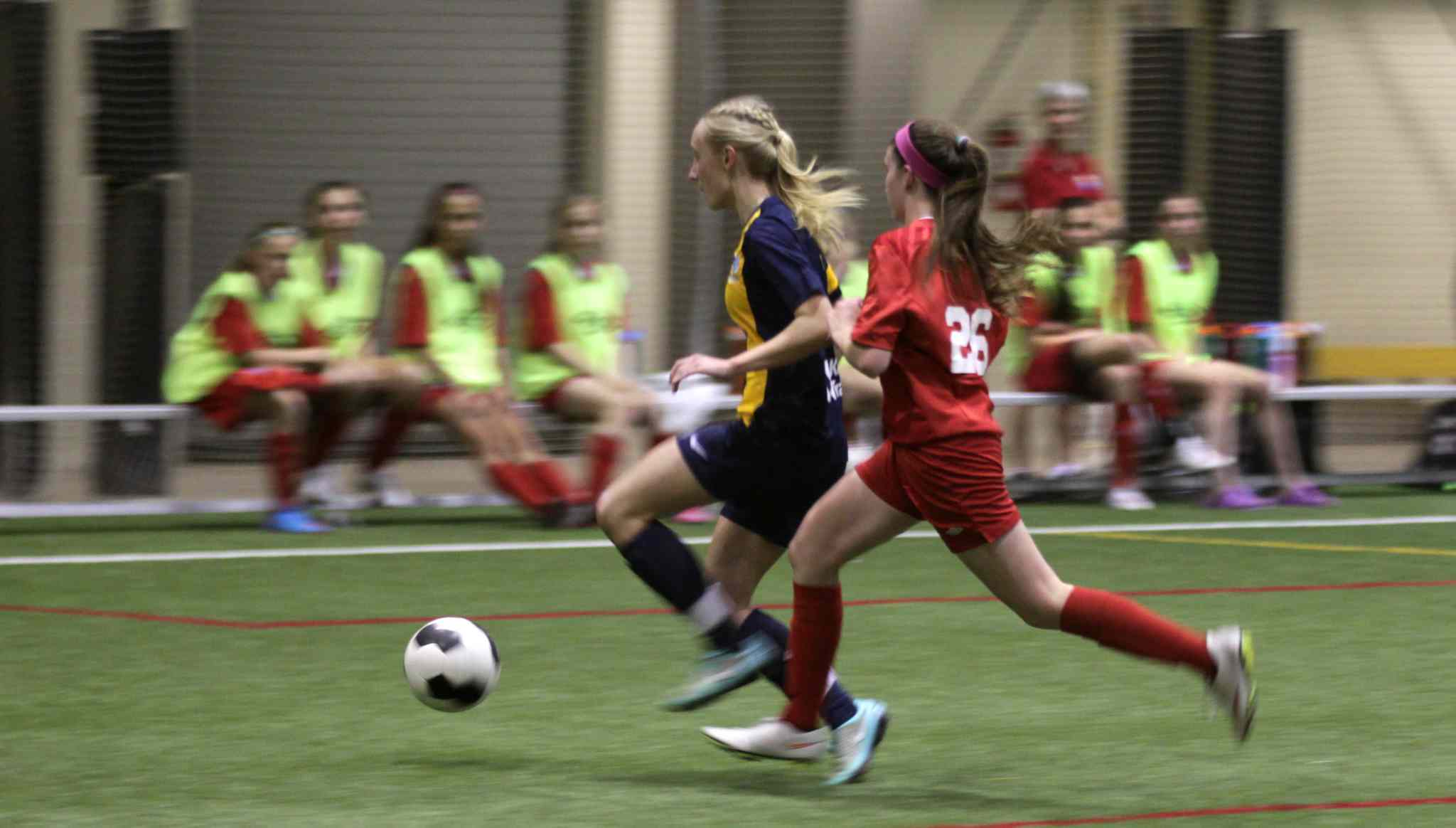 Australia's #7 Nickoletta Flannery (in blue) is pursued down the field by Bonivital's #26 Abby Laurin.
