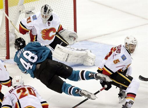 San Jose Sharks center Tomas Hertl (48), of the Czech Republic, is tripped by Calgary Flames defenseman Mark Giordano (5) as Hertl shoots during the second period of an NHL hockey game Wednesday, Nov. 26, 2014, in San Jose, Calif. (AP Photo/Marcio Jose Sanchez)