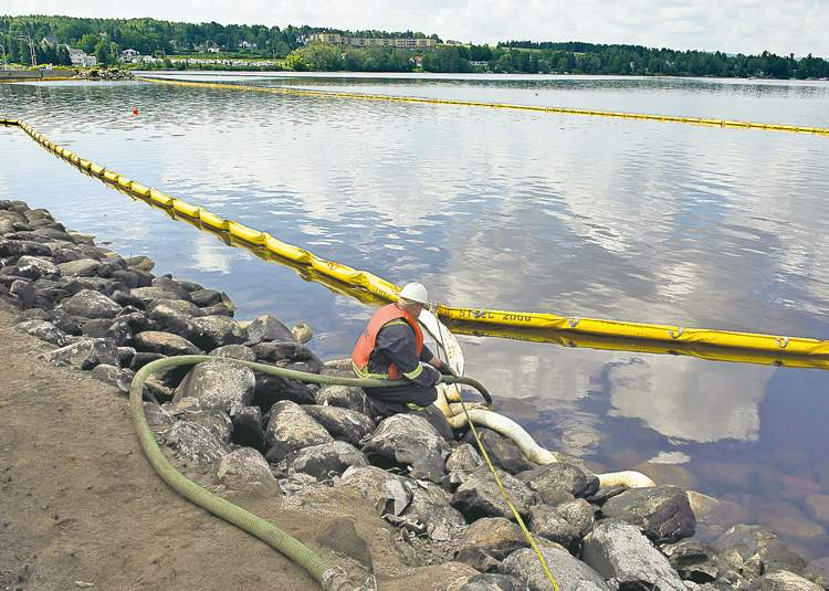 Cleanup crews pump oil from the shore of Lac-M��gantic as work continues at the site of the train derailment and fire.