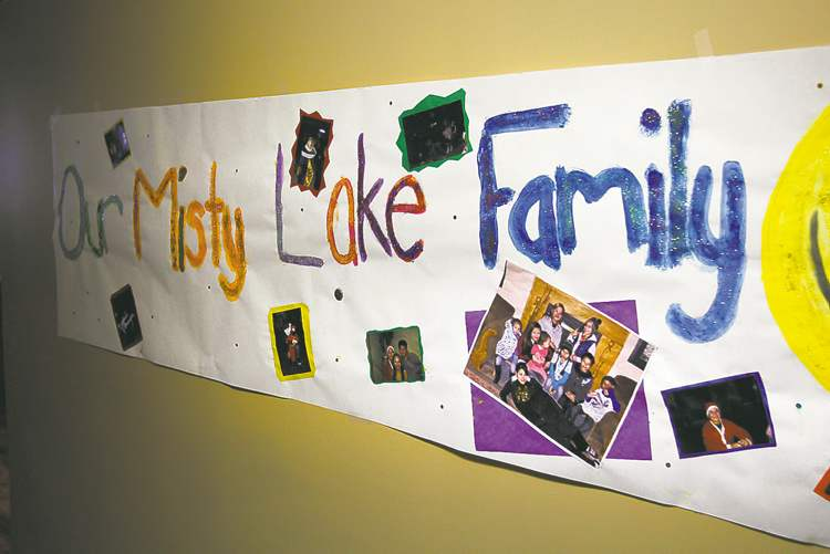 Little Saskatchewan evacuees at the Misty Lake Lodge last December with signs they made in the hallway of the lodge.