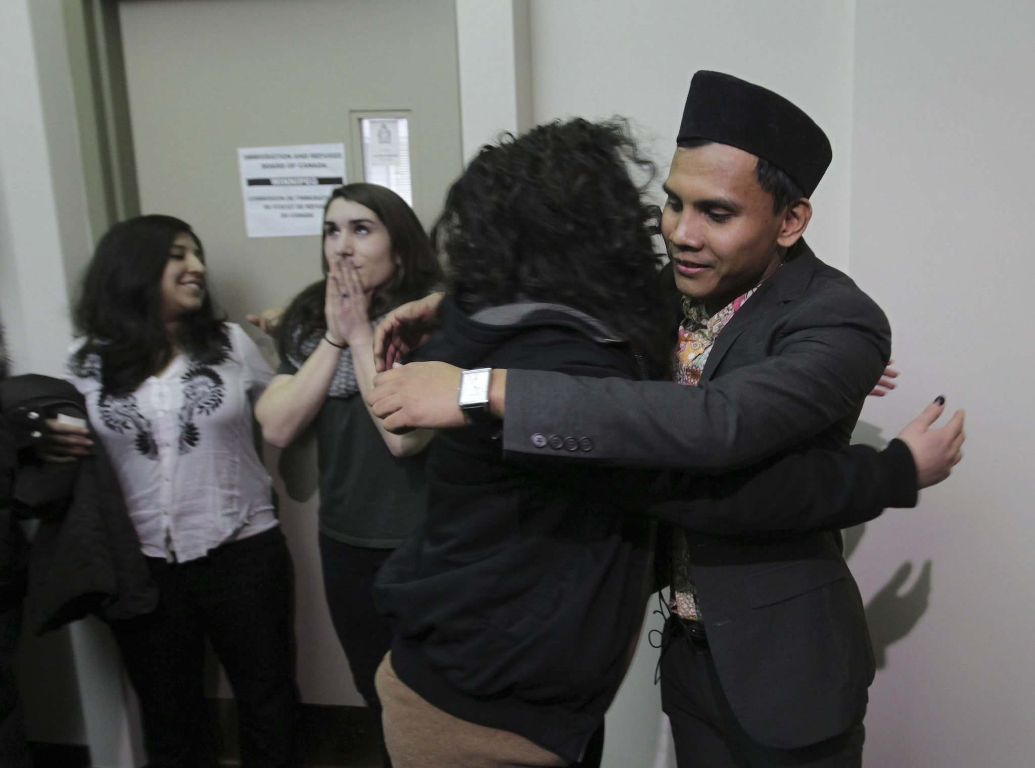 Malaysian student Hazim Ismail (right) gets a hug from Alexa Potashnik outside the refugee hearing office in Winnipeg Tuesday morning after winning his case against being deported back to Malaysia, where he had been given death threats due to his sexual orientation. </p>