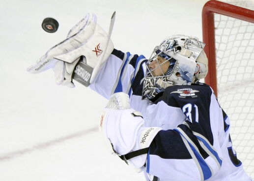 Winnipeg Jets' goaltender Ondrej Pavelec deflects the puck during the third period of an NHL hockey game against the New Jersey Devils Thursday, Oct. 30, 2014, in Newark, N.J. The Devils won 2-1 in a shootout.
