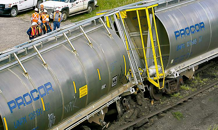 Rail cars sit next to the tracks after a 2010 derailment in Brandon.