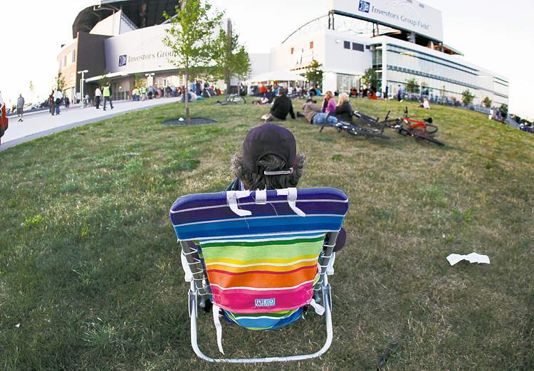 John Woods / Winnipeg Free Press A thrifty fan gets to listen for free to the Paul McCartney concert outside Investors Group Field Monday evening.