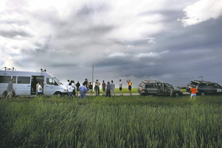 The rolling hills northeast of Calgary draw a large crowd of storm-chasers hot on the trail of a supercell under scorching heat and looming darkness.