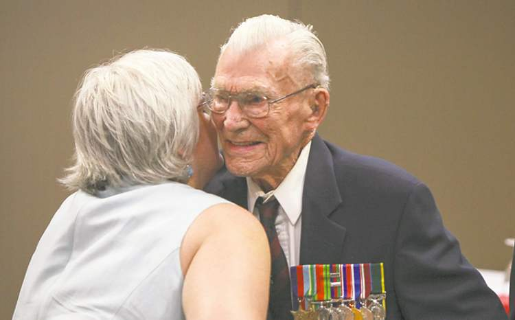 George  Peterson (centre), the sole surviving member of the Arden Seven, receives a hug from Christine Melnick, MLA for Riel, during the dedication of a new park plaza in honour of seven comrades who grew up on Arden Ave. in Winnipeg. They volunteered, fought and were captured during the Battle of Hong Kong during the Second World War in 1941. The Arden Seven Interpretive Plaza, to be located in Jules Mager Park in St. Vital, was announced at the Viscount Gort Hotel today by Premier Greg Selinger (right) and Mayor Sam Katz. It commemorates comrades Fred Abrahams, twins Morris and George Peterson, and brothers Alfred, Edward and Harry Shayler, and Bill Lancaster, all of whom survived the battle of Hong Kong. Friday, August 16, 2013.  (OLIVER SACHGAU) (JESSICA BURTNICK/WINNIPEG FREE PRESS)