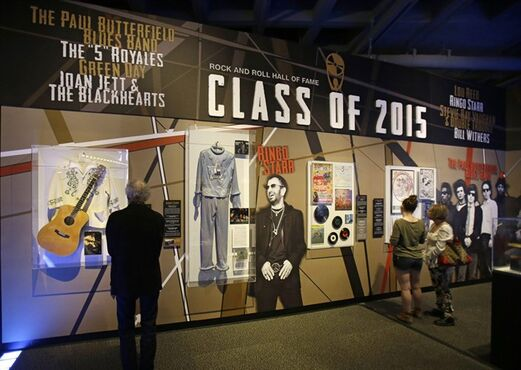 People look at the Class of 2015 exhibit at the The Rock and Roll Hall of Fame and Museum Friday, April 17, 2015, in Cleveland. Ringo Starr, who was previously enshrined with the Beatles in 1988, will be honored along with pop punks Green Day, soul singer-songwriter Bill Withers, underground icon Lou Reed, guitarist Stevie Ray Vaughan and Double Trouble, Joan Jett and The Blackhearts, The Paul Butterfield Blues Band and The