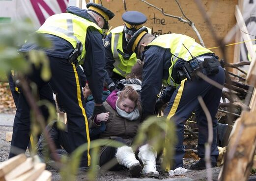RCMP officers take protesters into custody at an anti-pipeline demonstration in Burnaby, B.C., on Thursday, Nov. 20, 2014. THE CANADIAN PRESSA/Jonathan Hayward