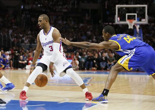 Los Angeles Clippers Chris Paul, left, dribbles between his legs while Golden State Warriors' Harrison Barnes, right, defends during the first half of an NBA basketball game, Tuesday, March 31, 2015, in Los Angeles. (AP Photo/Danny Moloshok)