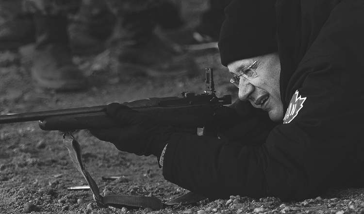 Prime Minister Harper shoots a .303 rifle while taking part in demonstration by Canadian Rangers near Gjoa Haven, Nunavut, on Tuesday.