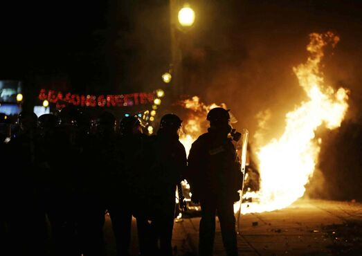 Police in riot gear move down the street past a burning police car, Monday, Nov. 24, 2014, in Ferguson, Mo. A grand jury has decided not to indict Ferguson police officer Darren Wilson in the shooting death of 18-year-old Michael Brown and some protesters have reacted violently.