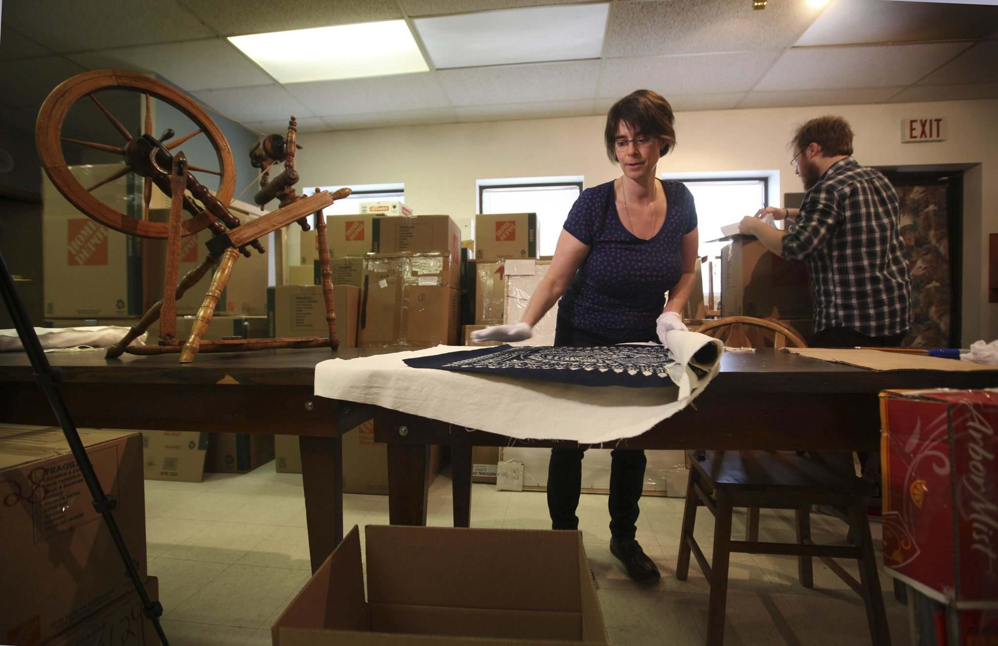RUTH BONNEVILLE / WINNIPEG FREE PRESS</p><p>Andrea Reichert, curator of the Manitoba Crafts Museum and Library, rolls up a large chinese Batik while curatorial assistant Eric Napier Strong packs articles into boxes for the museum&#39;s upcoming move.</p>