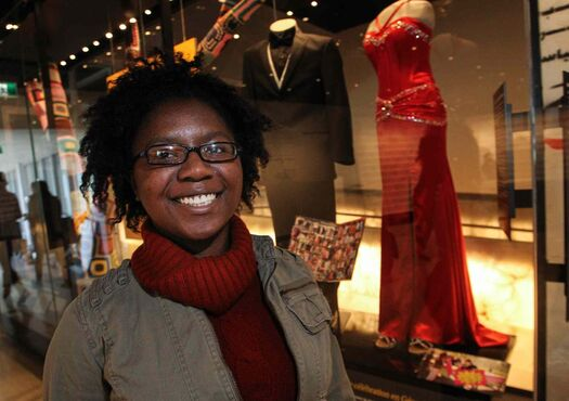 Mareshia Rucker is seen with her prom dress at the Canadian Museum for Human Rights in Winnipeg. Rucker organized the first-ever interracial prom in 2013 at her high school in Abbeville, Georgia. The red dress and shoes she wore are on display in the museum's