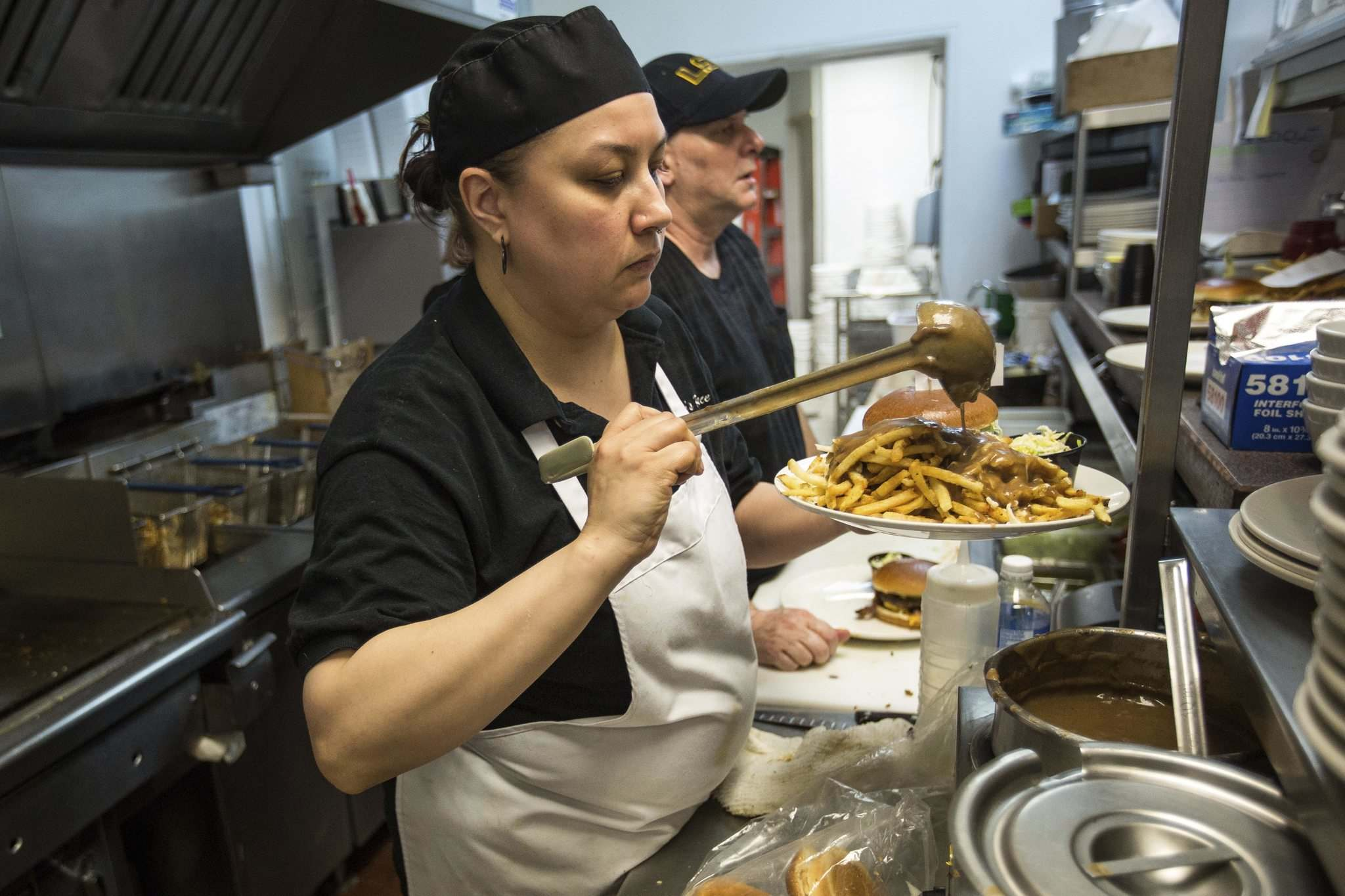 Cook Felicia puts the finishing touches on a lunch with fries by adding gravy.</p></p>