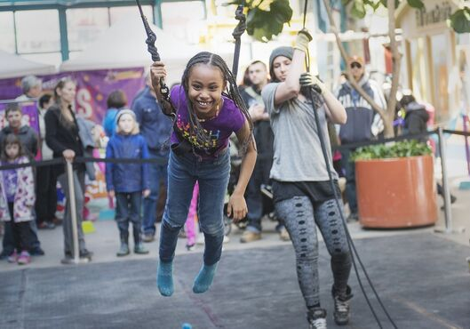 Deby Amare, 8, makes it back to the ground after she hangs from the trapeze at the Festival of Fools at The Forks on Sunday.