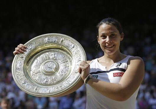 Marion Bartoli, of France, smiles as she holds the trophy after winning the women's singles final against Sabine Lisicki, of Germany, at the All England Lawn Tennis Championships in Wimbledon, London on July 6, 2013. Former Wimbledon champion Marion Bartoli has fuelled speculation of a possible comeback by asking her fans on social media if it would be a good idea. THE CANADIAN PRESS/AP, Anja Niedringhaus