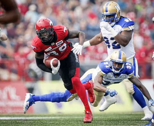 Winnipeg Blue Bombers' Drake Nevis, top right, and Brandon Alexander look on as Calgary Stampeders' DaVaris Daniels runs the ball in for a touchdown in August.