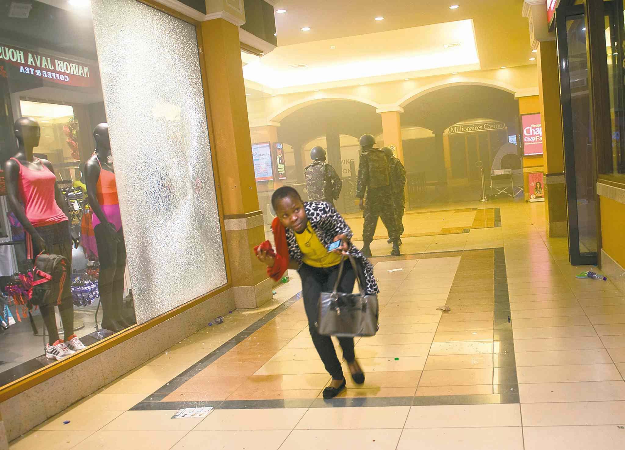 Jonathan Kalan / THE ASSOCIATED PRESSA woman who had been hiding during the gun battle runs for cover after armed police, seen behind, enter the Westgate Mall in Nairobi, Kenya, Saturday.