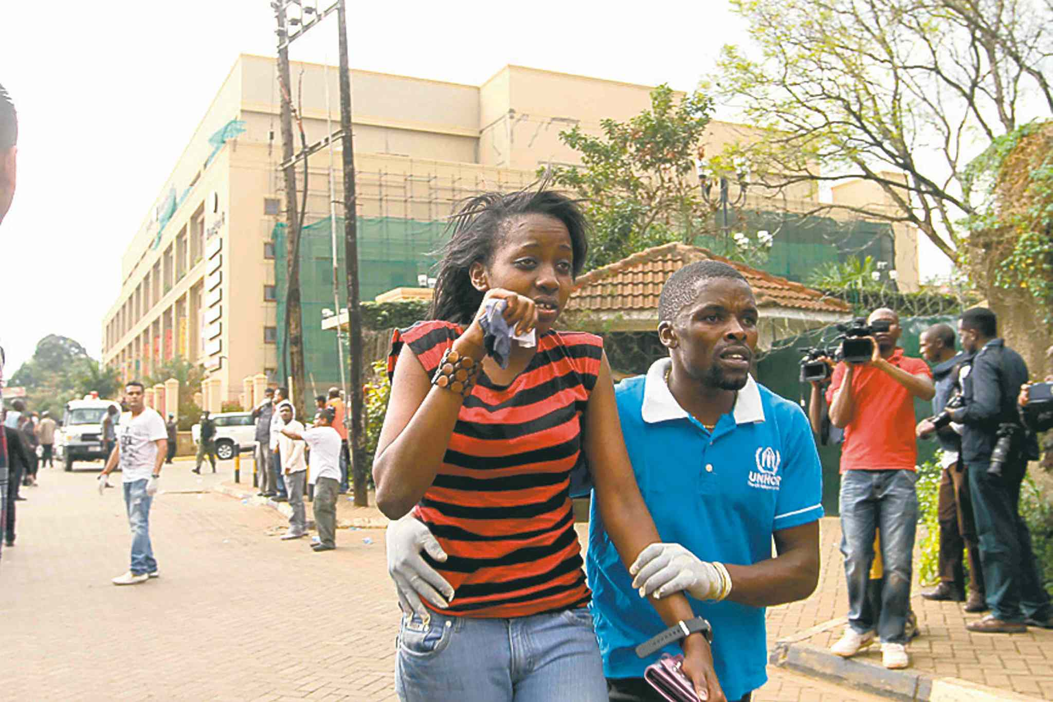 Fred Mutune / MCTA wounded woman is helped to safety outside Westgate Mall on Saturday, September 21, 2013, in Nairobi, Kenya.