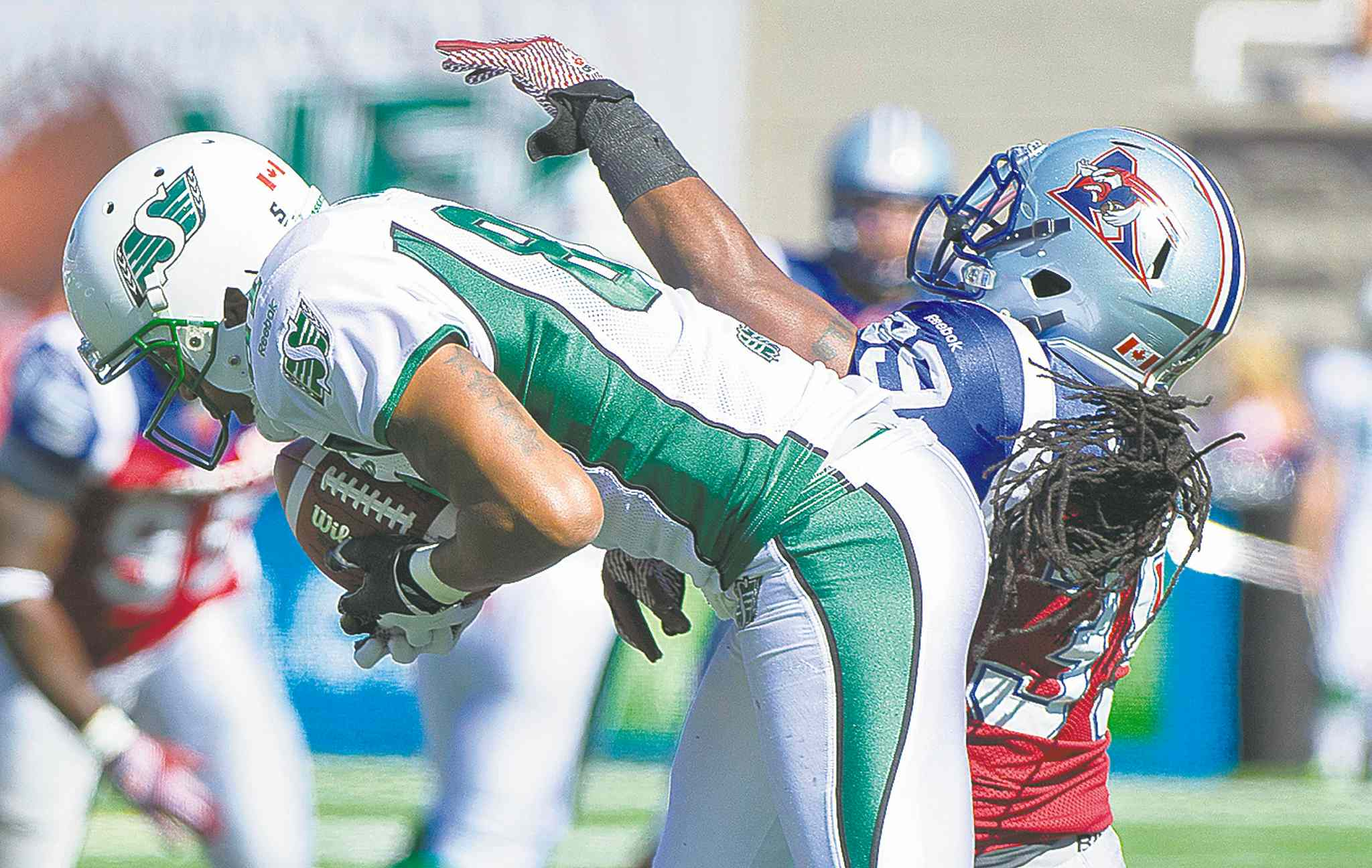 Geroy Simon makes a catch to break Ben Cahoon's all-time CFL catch record as Alouettes' Jerald Brown defends Sunday.